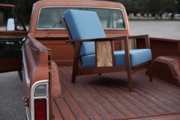 dark wood chair with blue cushion in truck bed